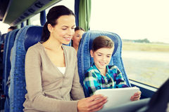 Happy family with tablet pc sitting in travel bus Stock Photo
