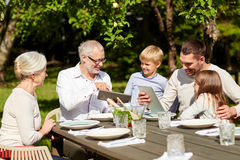 Happy family with tablet pc at table in garden Stock Images