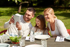 Happy family with tablet pc at table in garden Royalty Free Stock Photography