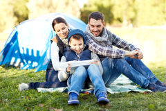 Happy family with tablet pc and tent at camp site Royalty Free Stock Photo