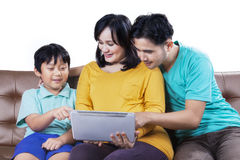 Happy family with tablet on sofa Royalty Free Stock Images