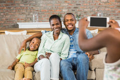 Happy family taking a picture on the couch. In living room Stock Photo