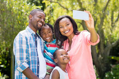 Happy family taking picture. At park Royalty Free Stock Image
