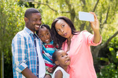 Happy family taking picture. Happy family taking a photo at park Royalty Free Stock Photo