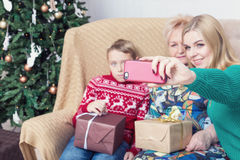 Happy family taking picture with smartphone on Chistmas decorations. Selective focus on smartphone Stock Photo
