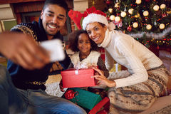 Happy family taking self portrait with smartphone during Christmas. Happy family taking self portrait with smartphone during Christmas at home royalty free stock photo