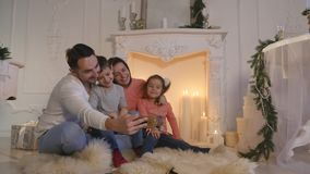 Happy family taking self portrait with smartphone during Christmas at home stock video footage