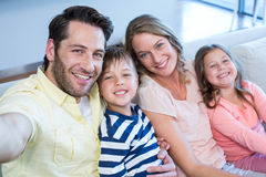 Happy family taking selfie on couch Royalty Free Stock Photos