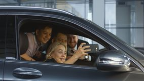 Happy family taking selfie in new. Cheerful couple with kids sitting in car and taking selfie with dealer enjoying successful purchase in salon. Movement stock photography