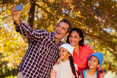 Happy family taking selfie at park. During autumn Royalty Free Stock Images