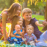 Happy family taking selfie  in park. Royalty Free Stock Image