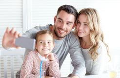 Happy family taking selfie at restaurant. Family, parenthood, technology and people concept - happy mother, father and little girl having dinner and taking stock photos