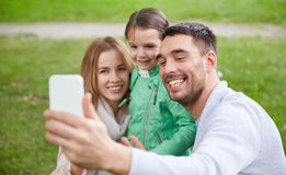 Happy family taking selfie by smartphone outdoors Royalty Free Stock Image