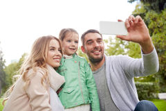 Happy family taking selfie by smartphone outdoors Stock Photography