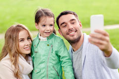 Happy family taking selfie by smartphone outdoors Royalty Free Stock Photography