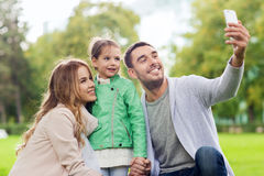 Happy family taking selfie by smartphone outdoors Royalty Free Stock Photos