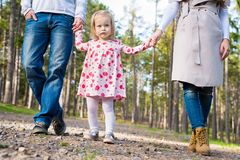 Happy family taking a walk in a park, family holding hands walking together along forrest path. Happy young family taking a walk in a park, family holding hands Royalty Free Stock Photography