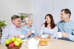 Happy family tea time at nursing home for elderly. Parents with children have fun talk communication and leisure. Senior couple. And relatives. Visit old mother stock photo