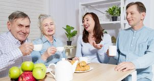 Happy family tea time at nursing home for elderly. Parents with children have fun talk communication and leisure. Senior couple. And relatives. Visit old mother stock image
