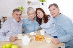 Happy family tea time at nursing home for elderly. Parents with children have fun talk communication and leisure. Senior couple. And relatives. Visit old mother stock images