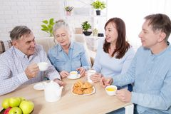 Happy family tea time at nursing home for elderly. Parents with children have fun talk communication and leisure. Senior couple. And relatives. Visit old mother stock photography