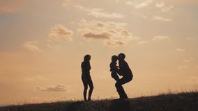 Happy family teamwork. Happy joyful father having fun throws up in the air child. father`s day. happy family father mom. And son lifestyle silhouette sunset stock video