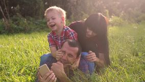 Happy family teamwork outdoors have fun concept outdoors slow motion video. mom dad and son take a photo lifestyle with. Smartphone in nature are sitting on the stock video footage