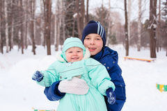 Happy family teenager and baby boy kid in winter park Royalty Free Stock Photography