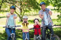 Happy family on their bike with thumbs up at the park Royalty Free Stock Photo