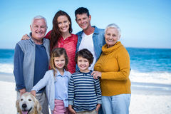 Happy family with their dog at the beach. On a sunny day Royalty Free Stock Image