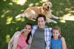 Happy family with their dog in the park Royalty Free Stock Photo