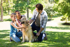 Happy family with their dog in the park Royalty Free Stock Photography