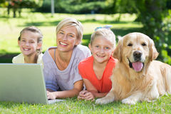 Happy family and their dog smiling at the camera Royalty Free Stock Image
