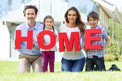 Happy family and their house. Portrait of happy smiling family and their children holding home letters near their house Royalty Free Stock Images