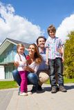 Happy family and their house. Portrait of happy smiling family and their children near their house Royalty Free Stock Photography