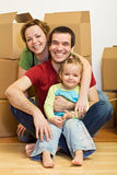 Happy family in their new home with lots of boxes Royalty Free Stock Image