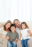 A happy family on their sofa looking at the camera Stock Images