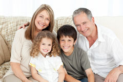 A happy family on their sofa looking at the camera Royalty Free Stock Image
