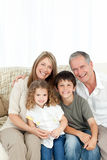 A happy family on their sofa looking at the camera Royalty Free Stock Photos