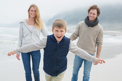 Happy family of three at the beach Stock Image