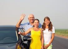 Happy family of three by car royalty free stock photo