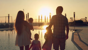 Happy family with three children admiring the sunset reflected in the surface of the pool Royalty Free Stock Image