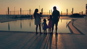 Happy family with three children admiring the sunset reflected in the surface of the pool Stock Photo