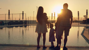 Happy family with three children admiring the sunset reflected in the surface of the pool Stock Photos