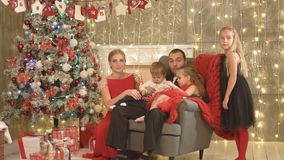 Happy family with three children sitting by the Christmas tree stock footage