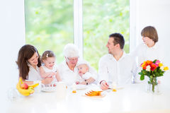 Happy family with three children visiting grandmother. Happy young family with three children - teenager boy, toddler girl and newborn baby - having fun together Royalty Free Stock Photos