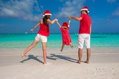Happy family of three in Christmas Hats during Royalty Free Stock Photography