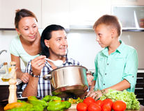 Happy family of three cooking lunch Stock Photos