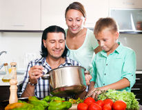 Happy family of three cooking vegetables Royalty Free Stock Photography