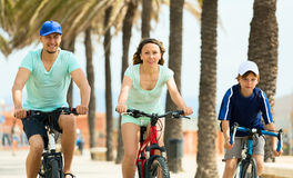 Happy family of three cycling across city Royalty Free Stock Photography